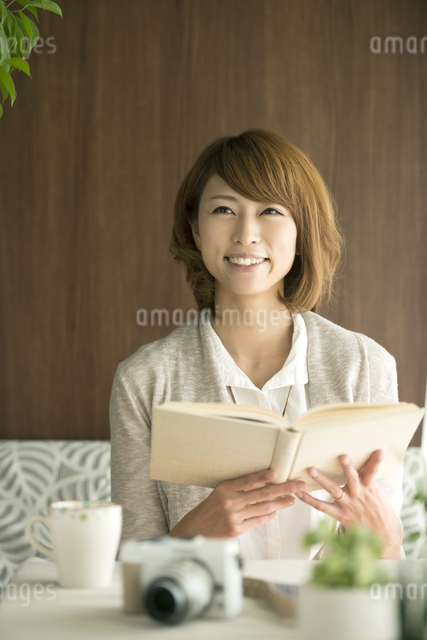 本を持ち微笑む女性の写真素材 [FYI04553175]