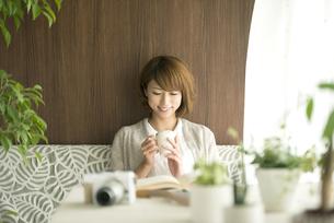 コーヒーカップを持ち微笑む女性の写真素材 [FYI04553179]