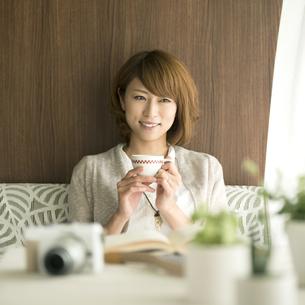 コーヒーカップを持ち微笑む女性の写真素材 [FYI04553181]