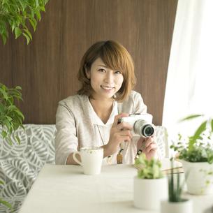 ミラーレス一眼カメラを持ち微笑む女性の写真素材 [FYI04553184]
