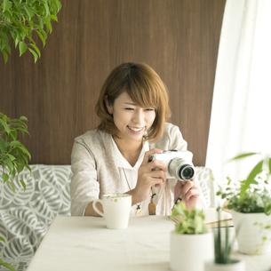 ミラーレス一眼カメラで写真を撮る女性の写真素材 [FYI04553192]