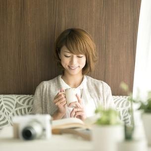 コーヒーカップを持ち微笑む女性の写真素材 [FYI04553200]