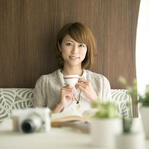 コーヒーカップを持ち微笑む女性の写真素材 [FYI04553201]