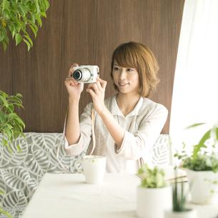 ミラーレス一眼カメラで写真を撮る女性の写真素材 [FYI04553204]