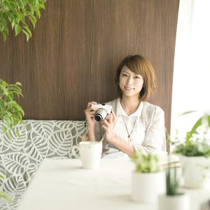 ミラーレス一眼カメラを持ち微笑む女性の写真素材 [FYI04553206]