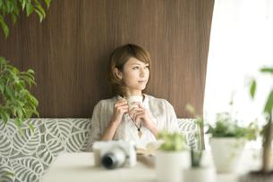 コーヒーカップを持ち窓の外を眺める女性の写真素材 [FYI04553223]