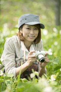 ミラーレス一眼カメラを持ち微笑む女性の写真素材 [FYI04553226]