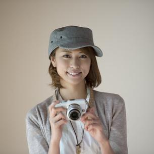 ミラーレス一眼カメラを持ち微笑む女性の写真素材 [FYI04553232]