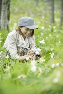 ミラーレス一眼カメラで植物の写真を撮る女性の写真素材 [FYI04553233]