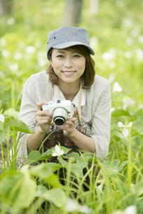 ミラーレス一眼カメラを持ち微笑む女性の写真素材 [FYI04553235]