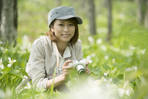 ミラーレス一眼カメラを持ち微笑む女性の写真素材 [FYI04553238]