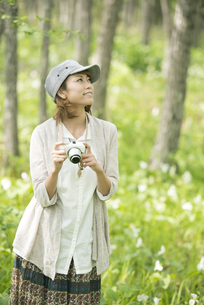 ミラーレス一眼カメラを持ち微笑む女性の写真素材 [FYI04553240]