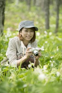 ミラーレス一眼カメラを持ち微笑む女性の写真素材 [FYI04553241]