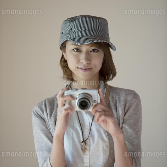ミラーレス一眼カメラを持ち微笑む女性の写真素材 [FYI04553242]