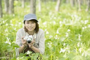 ミラーレス一眼カメラを持ち微笑む女性の写真素材 [FYI04553250]