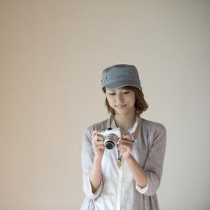 ミラーレス一眼カメラを見る女性の写真素材 [FYI04553251]