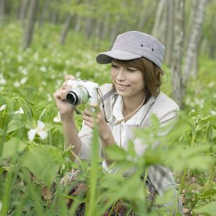 ミラーレス一眼カメラで植物の写真を撮る女性の写真素材 [FYI04553259]