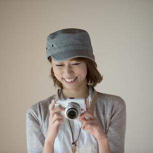 ミラーレス一眼カメラを見る女性の写真素材 [FYI04553266]
