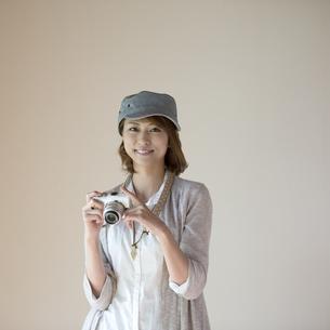 ミラーレス一眼カメラを持ち微笑む女性の写真素材 [FYI04553275]