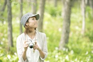 ミラーレス一眼カメラを持ち微笑む女性の写真素材 [FYI04553278]