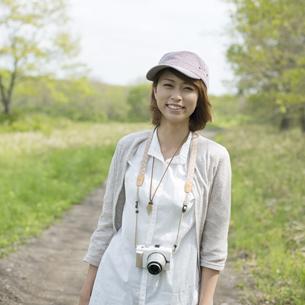 一本道で微笑む女性の写真素材 [FYI04553282]