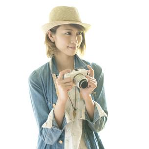 ミラーレス一眼カメラを持ち微笑む女性の写真素材 [FYI04553283]
