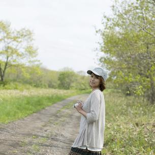 ミラーレス一眼カメラを持ち一本道で振り返る女性の写真素材 [FYI04553289]