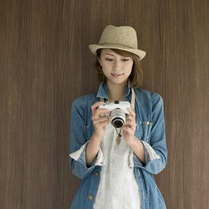 ミラーレス一眼カメラを見る女性の写真素材 [FYI04553291]
