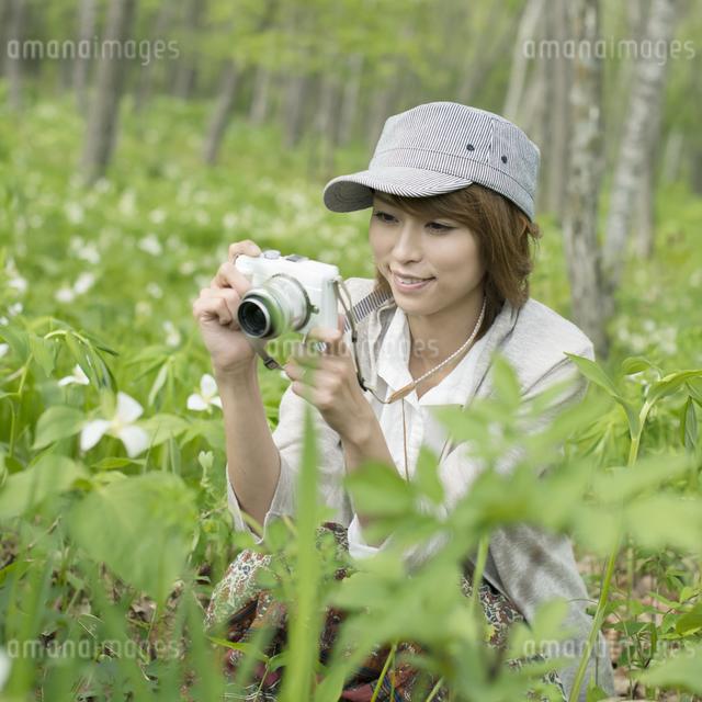 ミラーレス一眼カメラで植物の写真を撮る女性の写真素材 [FYI04553292]