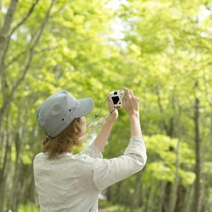 ミラーレス一眼カメラで写真を撮る女性の後姿の写真素材 [FYI04553293]