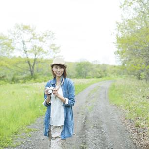 ミラーレス一眼カメラを持ち一本道を歩く女性の写真素材 [FYI04553295]