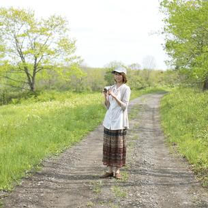 一本道でミラーレス一眼カメラを持ち微笑む女性の写真素材 [FYI04553296]
