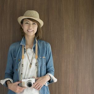 ミラーレス一眼カメラを持ち微笑む女性の写真素材 [FYI04553297]