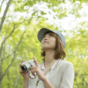 ミラーレス一眼カメラを持ち上を見上げる女性の写真素材 [FYI04553298]