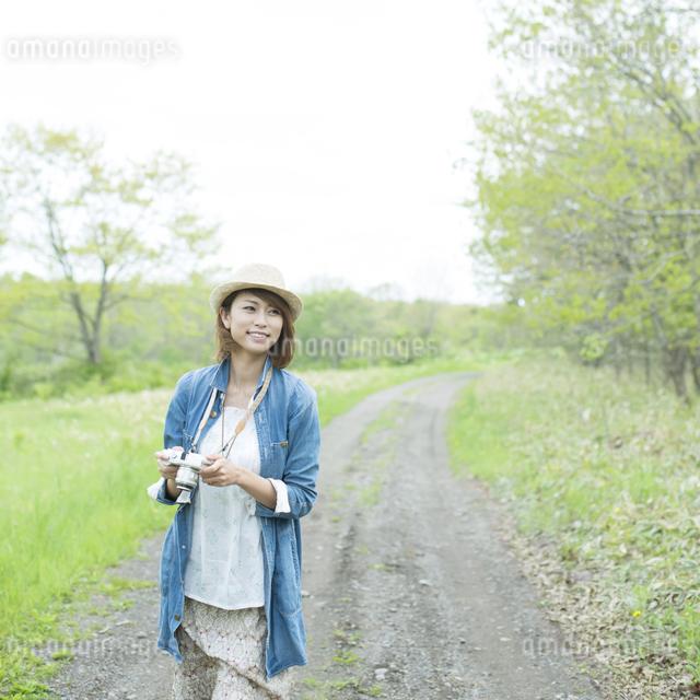 ミラーレス一眼カメラを持ち一本道を歩く女性の写真素材 [FYI04553299]