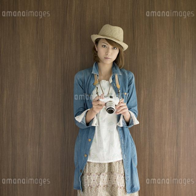 ミラーレス一眼カメラを持つ女性のポートレートの写真素材 [FYI04553303]