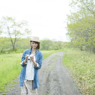 ミラーレス一眼カメラを持ち一本道を歩く女性の写真素材 [FYI04553304]