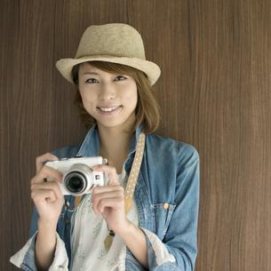 ミラーレス一眼カメラを持ち微笑む女性の写真素材 [FYI04553305]