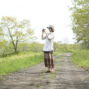 一本道で写真を撮る女性の写真素材 [FYI04553306]
