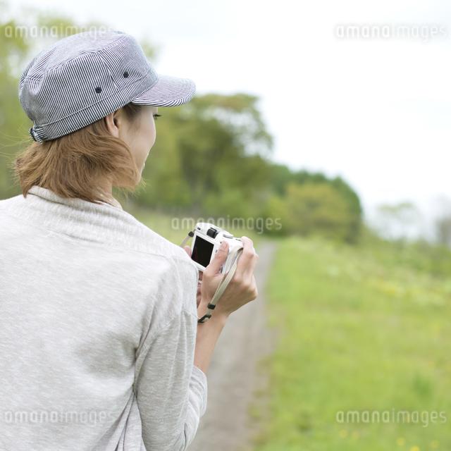 ミラーレス一眼カメラを持つ女性の後姿の写真素材 [FYI04553307]