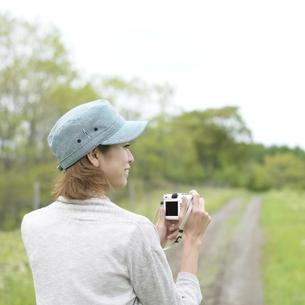 ミラーレス一眼カメラを持つ女性の後姿の写真素材 [FYI04553308]