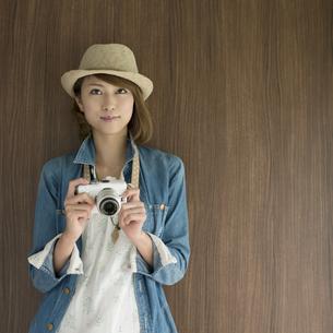 ミラーレス一眼カメラを持ち微笑む女性の写真素材 [FYI04553309]