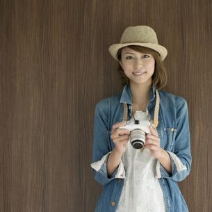 ミラーレス一眼カメラを持ち微笑む女性の写真素材 [FYI04553311]