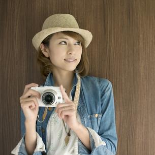 ミラーレス一眼カメラを持ち微笑む女性の写真素材 [FYI04553312]