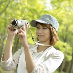 ミラーレス一眼カメラで写真を撮る女性の写真素材 [FYI04553314]