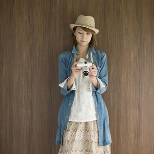 ミラーレス一眼カメラを見る女性の写真素材 [FYI04553315]