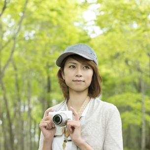 ミラーレス一眼カメラを持ち微笑む女性の写真素材 [FYI04553317]