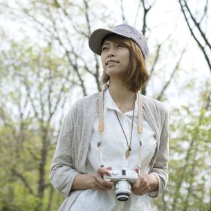 ミラーレス一眼カメラを持ち微笑む女性の写真素材 [FYI04553320]