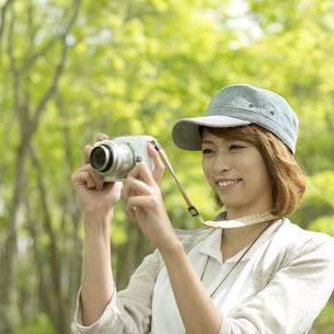 ミラーレス一眼カメラで写真を撮る女性の写真素材 [FYI04553321]