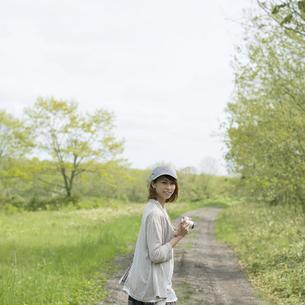 ミラーレス一眼カメラを持ち一本道で振り返る女性の写真素材 [FYI04553322]